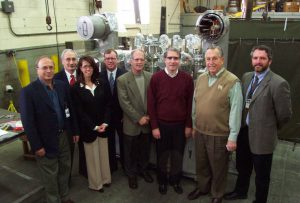 Left to Right: Joseph Rasson (Berkeley Lab), Bruce Strauss (DOE-Office of High Energy Physics), Eileen Cunningham (Meyer Tool), Jim Brosnahan (IL State Representative), Tom Peterson (Fermilab), Phil Pfund (Fermilab), Frank Meyer (President Meyer Tool) and Jim Kerby (Fermilab) stand in front of the first completed distribution box.
