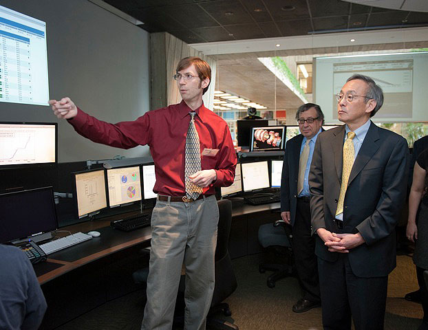 Fermilab scientist Aron Soha, front, and US CMS Project Manager Joel Butler, back, give Energy Secretary Steven Chu a tour of Fermilab's Remote Operations Center. US CMS scientists use Fermilab's ROC to monitor data coming from the CMS experiment at the LHC. Photo: Reidar Hahn.