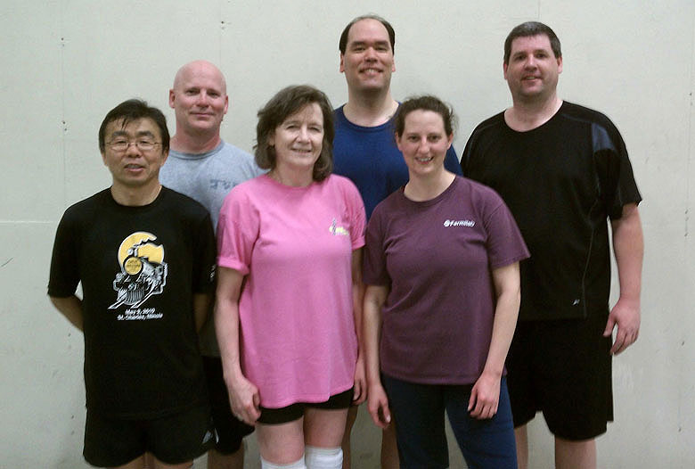 """The volleyball team """"Playing Havoc"""" won the 2010-2011 season championship of the competitive winter volleyball league. Front row from left: Taka Yasuda, PPD; Sue Grommes, DIR; Michelle Prewitt, Rice University. Back row from left: Rick Jesik, Imperial College; Mark Mattson, Wayne State University; and captain Geoff Savage, PPD."""