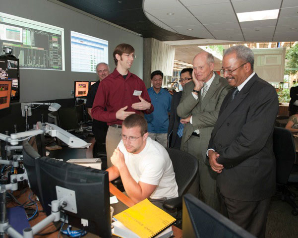 Fermilab scientist Aron Soha (left, in red shirt) explains to Congressman Chaka Fattah (far right) how the LHC Remote Operations Center is used to monitor the CMS experiment at CERN on his tour of Fermilab on July 18. His visit also included stops at the MINOS Underground Facility and the Superconducting Radio Frequency Test Facility. Also pictured are (left to right) Fermilab's Erik Gottschalk, University of Maryland's Jaime Gomez, Carnegie Mellon's Dongwook Jang, the DOE's congressional liason Clarence Tong and the DOE's director of the science office Bill Brinkman.