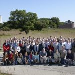More than 140 scientists, engineers, technical specialists and students from Brazil, Greece, Poland, the United Kingdom and the United States are involved in the MINOS experiment. This photo shows some of them posing for a group photo at Fermilab, with the 16-story Wilson Hall and the spiral-shaped MINOS service building in the background.
