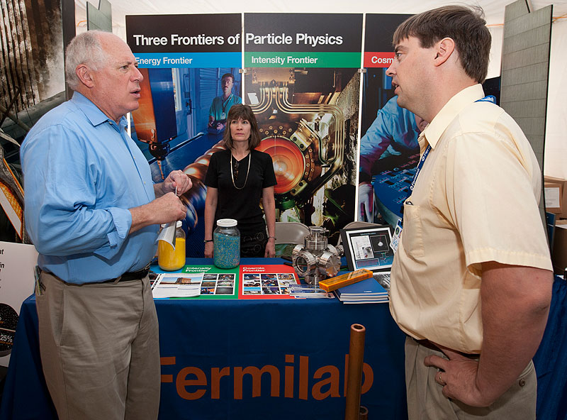 "Illinois Governor Pat Quinn talks with Fermilab scientist Chris Polly at Fermilab's booth in the Governor's tent ""Illinois Innovation!"" at the Illinois State Fair on Aug. 11. Fermilab will staff a booth at the fair through this weekend. Photo: Reidar Hahn"