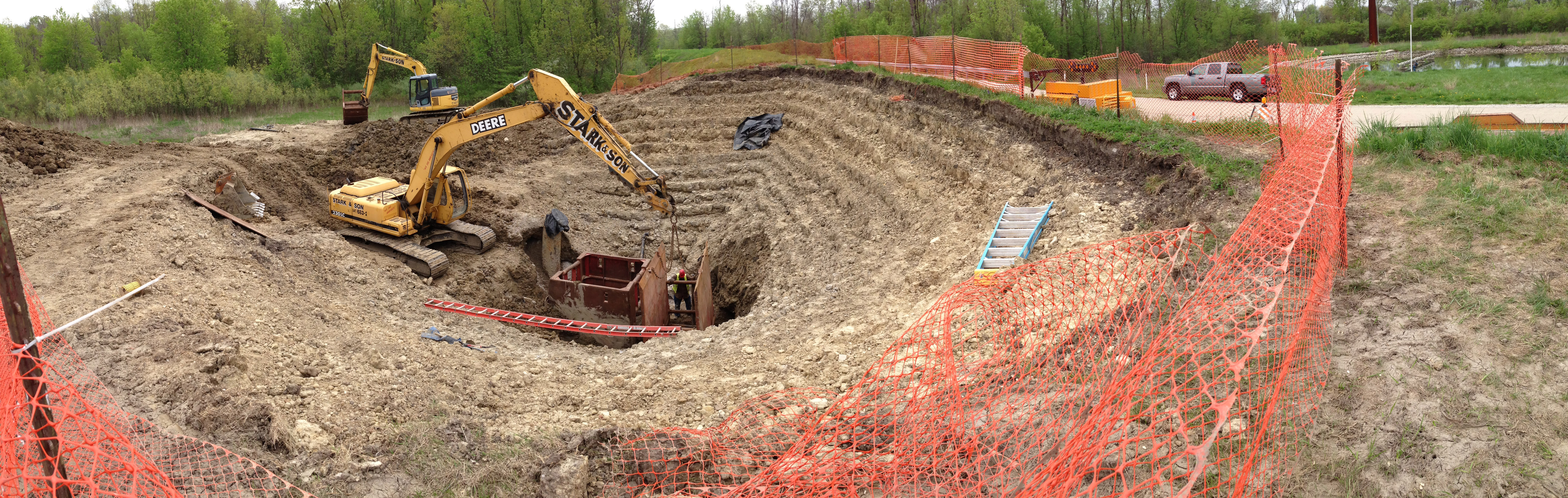In May, contractor Stark and Son began fixing a broken utility pipe that for years had been taking in soil through a break in the pipe wall, facilitating the growth of a pre-existing sinkhole. The hole pictured was on the Main Injector berm between MI31 and MI39. Workers used the track hoe pictured to dig a hole roughly 25 feet deep. For scale, the worker in the middle of the hole is about 6 feet tall. Photo: Larry Sliwa, FESS
