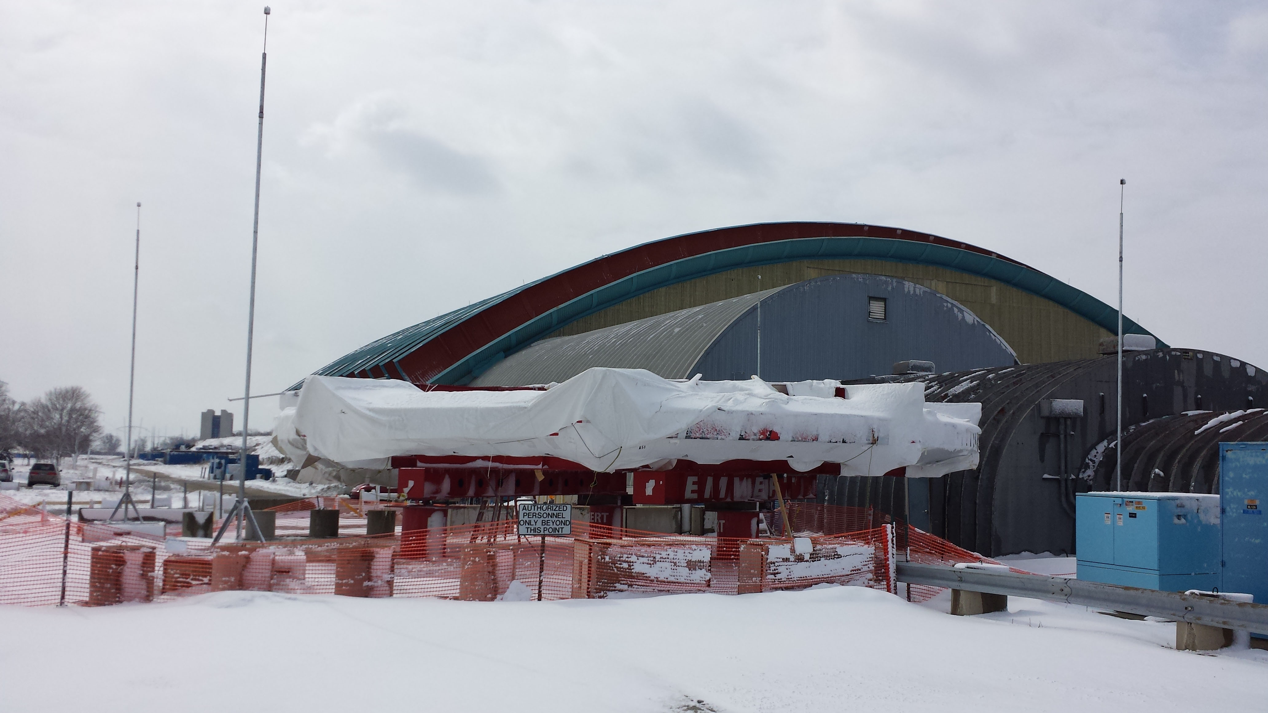 The Muon g-2 ring sits on a small patch of concrete cleared of snow by the Test Beam Facility. Once the MC-1 Building is complete, the ring will have a new indoor home. Fermilab Today periodically runs updates on the construction of the MC-1 Building. Photo: Julius Borchert, BSS