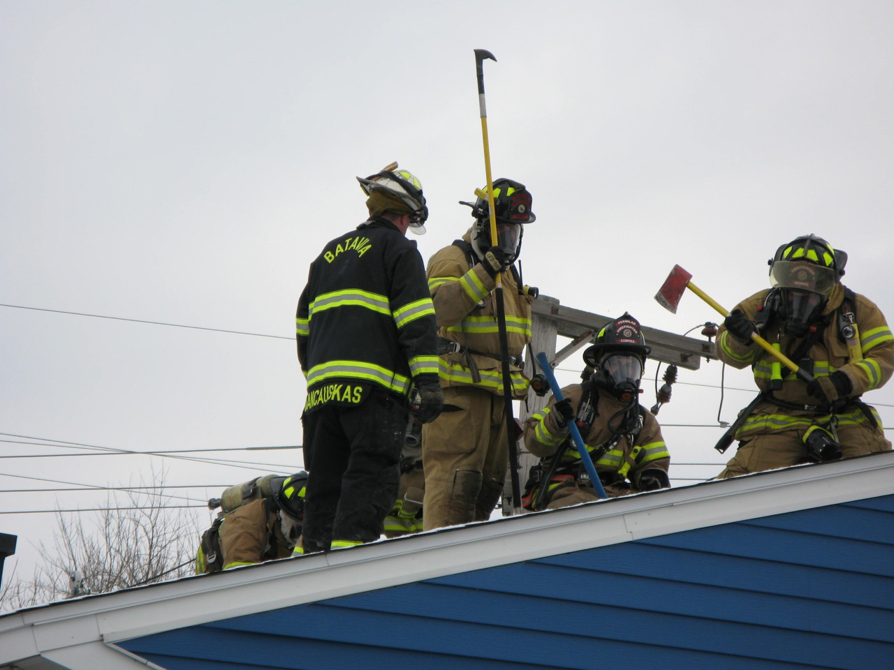 Last week, the Batavia, Fermilab and Warrenville fire departments conducted training exercises in the Village. FESS is removing materials from buildings scheduled to be demolished to be reused in similar structures elsewhere. The fire departments made use of these near-end-of-life buildings, running emergency drills in and on them. Here the Batavia fire chief joins Fermilab firefighters as they cut into one building's roof. Photo: Chuck Kuhn, BSS