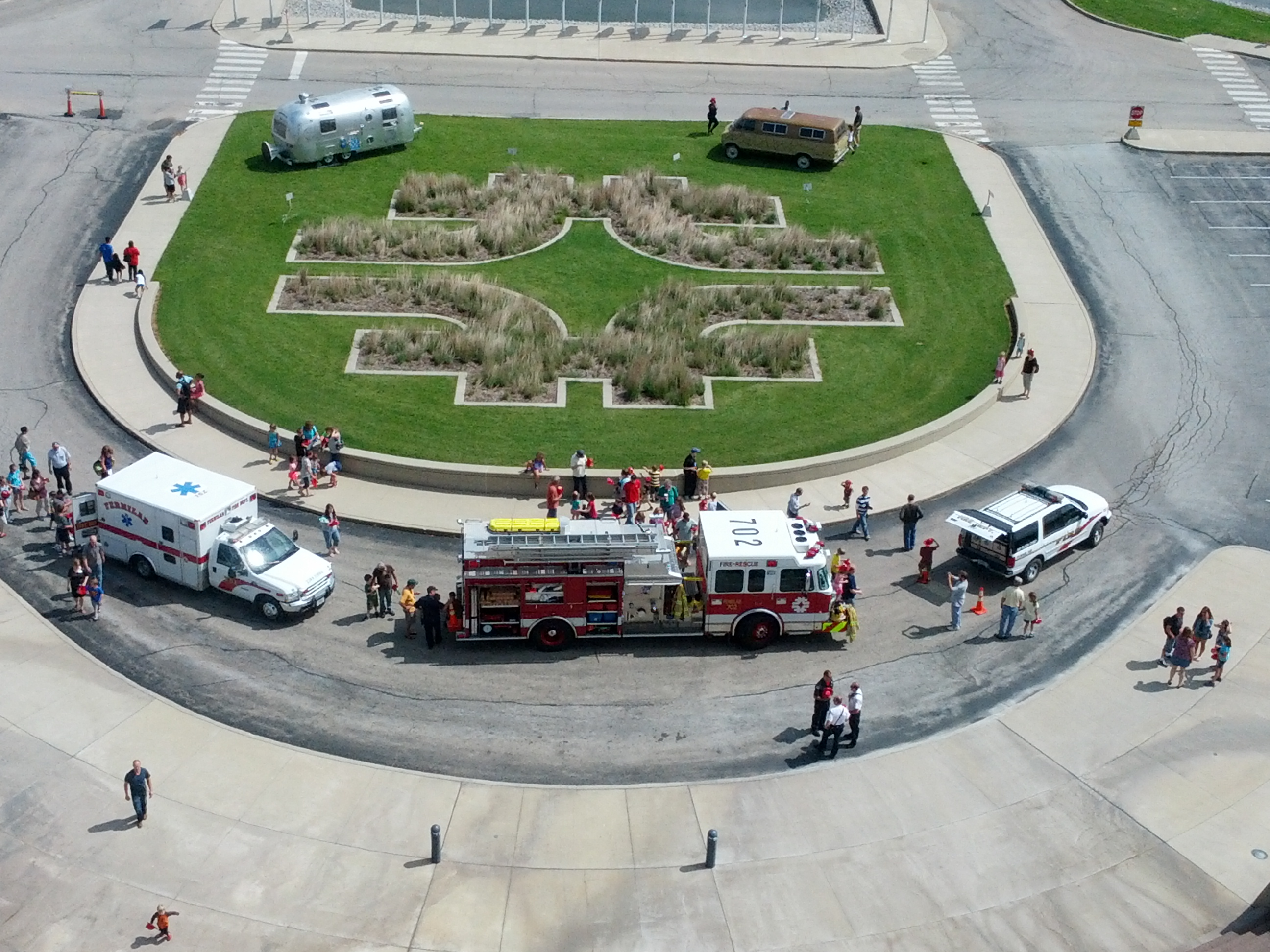 On Daughters and Sons to Work Day, five vehicles formed a ring around the front lawn of Wilson Hall. Counter-clockwise from top left: Edward Tufte's Interplanetary Explorer, the Fermilab ambulance, the Fermilab firetruck, the Fermilab battalion chief's vehicle and the Feynman van. Photo: Ken Schumacher, SCD