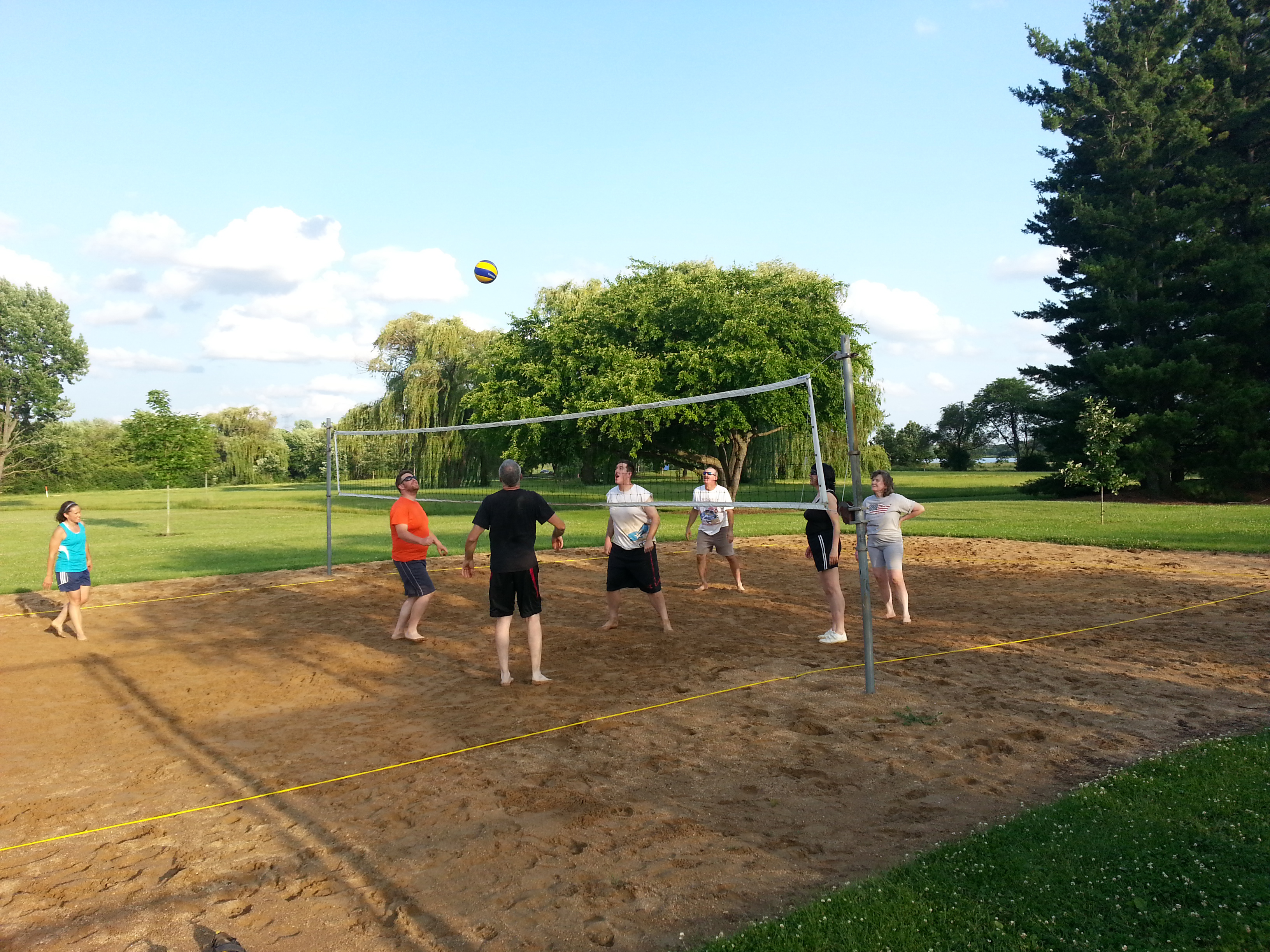 Fermilab staff serve, pass and block during an energetic pickup volleyball game at the Village sand courts. Pickup volleyball games take place on Tuesdays at 5:30 p.m. throughout the summer. All are welcome to join the fun. Bring comfortable clothes and shoes. Photo: Joseph Brown, AD
