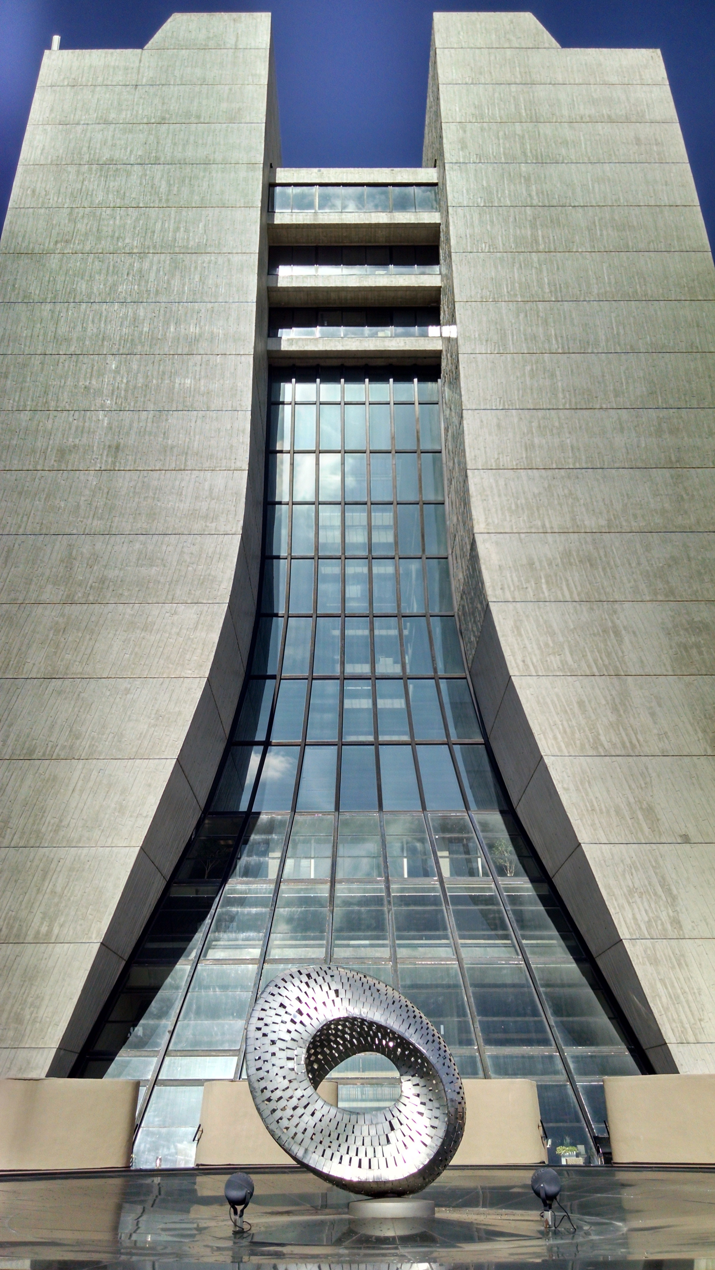 """Mobius Strip"" and the windows of Wilson Hall gleam in the sunlight."