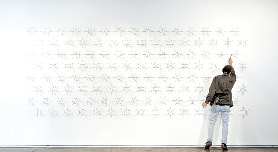 Edward Tufte makes an adjustment to one of his large-scale pieces based on Feynman diagrams.