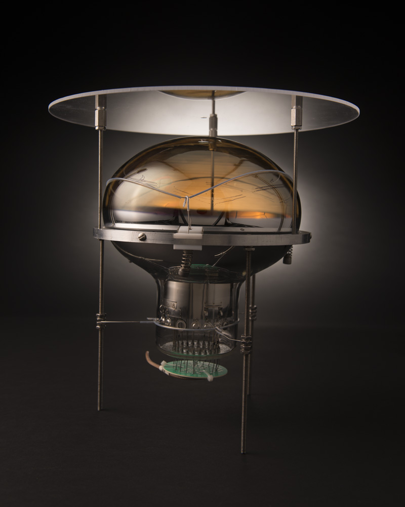 This is a mechanical model of one of the 32 photomultiplier tubes that are strung along the interior walls of the MicroBooNE detector. When a neutrino collides with an argon nucleus in the MicroBooNE detector, the resulting charged particles excite the argon to produce photons. The photons will travel to a photomultiplier tube such as the one pictured. As the name suggests, a photomultiplier amplifies the light signal, and the signal is then read out by a computer. The data from the photons give information about the location and energy of the original neutrino interaction. Photo: Reidar Hahn