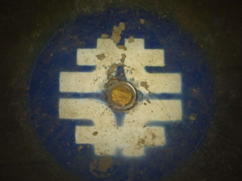 This quadrupole-dipole Fermilab logo can be found on the floor of the Tevatron tunnel. Photo: Amy Scroggins, Abri Credit Union
