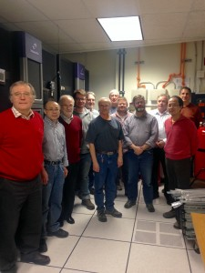 Data Movement and Storage Department stand in the FCC tape robot room. From left: Alex Kulyavtsev, Yujun Wu, Albert Rossi, Dmitri Litvintsev, Gene Oleynik, John Hendry, Stan Naymola, Tim Messer, Terry Jones, Alexander Moibenko, Chih-Hao Huang, Paul Tader. Not pictured are Gerard Bernabeu and George Szmuksta. Photo courtesy of Hannah Ward, OCIO