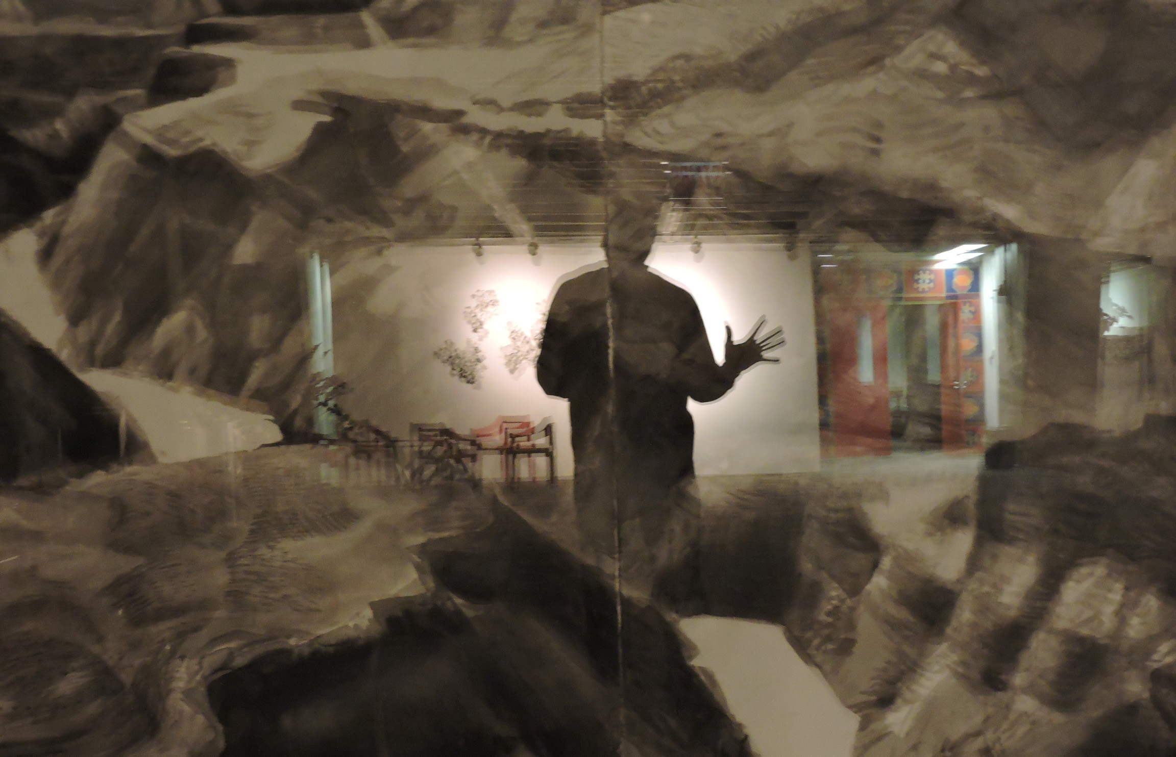 """The photographer's reflection appears in the glass that covers Martyl Langsdorf's painting """"The Canyon,"""" on display in the Fermilab Art Gallery. Photo: Rick Meaderdes, ESH&Q"""