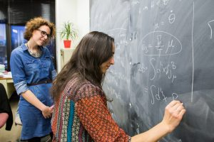 Pilar Coloma (left) and Seyda Ipek write calculations from floor to ceiling as they try to find solutions to lingering questions in our current models of the universe. Photo: Rashmi Shivni, OC