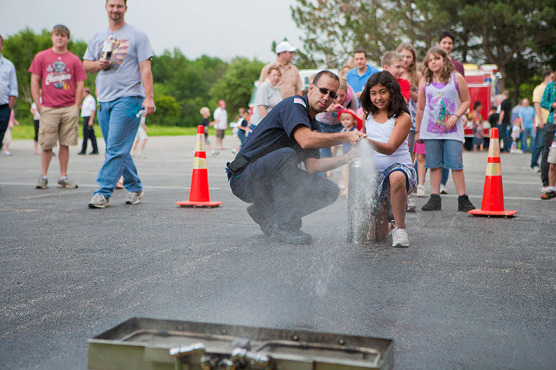 A firefighter helps a young girl put out a fire using a fire hose. The activity was part of a demonstration on fire prevention and safety held during DASTOW on June 23. More images of the DASTOW events are available online. Photo: Cindy Arnold