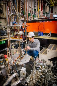 Sam Posen sets up a superconducting accelerating cavity in a vertical test stand. Photo: Reidar Hahn