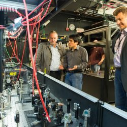 Fermilab accelerator scientist Jinhao Ruan (center) shows Fermilab Director Nigel Lockyer (left) the laser setup for the FAST photoinjector. Vladimir Shiltsev (right) is director of the Fermilab Accelerator Physics Center. Photo: Reidar Hahn
