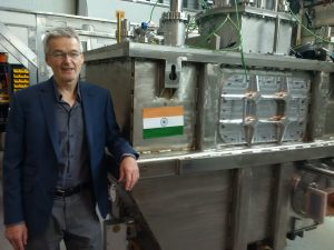 Bob Laxdal smiling next to his superconducting cryomodule. Photo courtesy of Nigel Lockyer