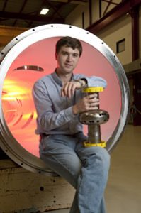 Alex Romanenko, sitting on the edge of a large cryogenic vessel, holds one of the superconducting RF cavities made of niobium. Photo: Fermilab (Click on image for larger version)