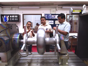 From left: Kishore Mistry (IUAC), Sumit Som (VECC) and P.N. Prakash (IUAC) inspect an accelerating cavity at the electron beam welding facility at the Inter-University Accelerator Center in Delhi, India. Photo courtesy of Sumit Som