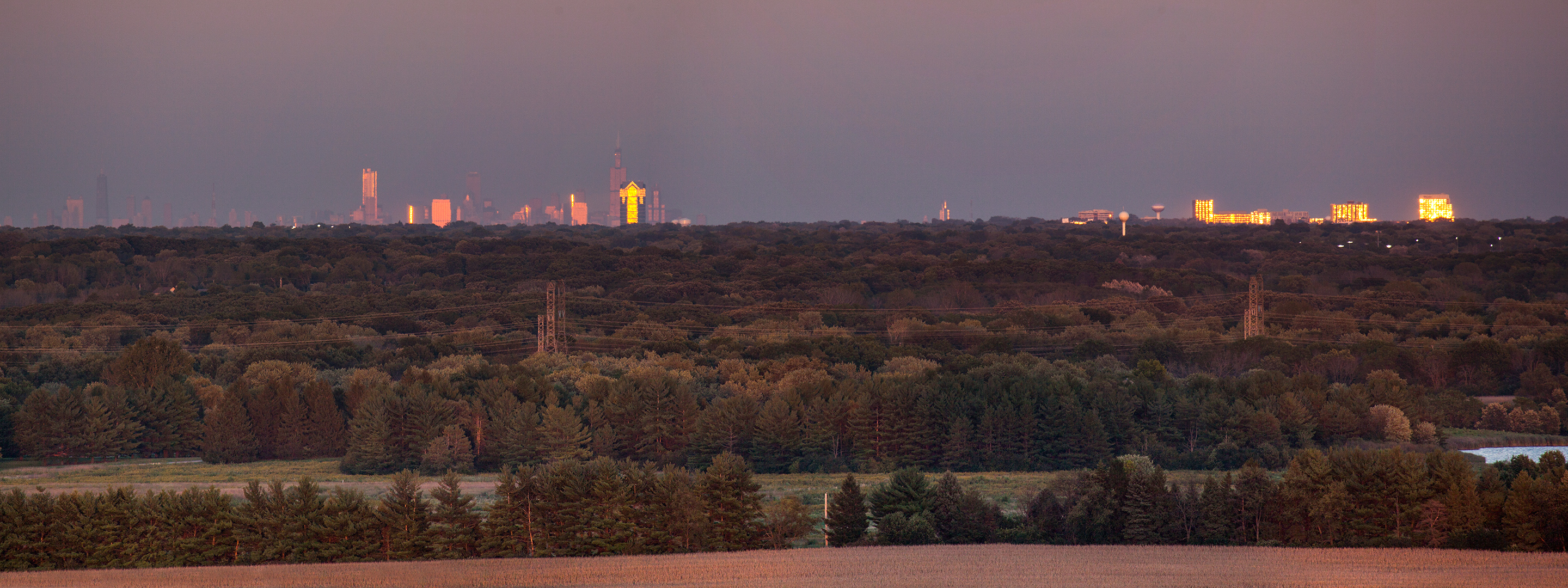 From atop Wilson Hall, you can see, from left, the Chicago skyline, Terrace Tower in Oak Brook and buildings in Naperville shimmering in late afternoon sunlight. Photo: Marty Murphy