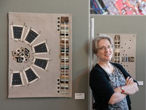 """Lindsay Olson stands by """"Discoveries,"""" a textile piece. Photo: Bree Corn"""