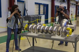 Two photographers capture on camera a nine-cell superconducting radio-frequency cavity in the Industrial Building Complex. Photo: Cindy Arnold