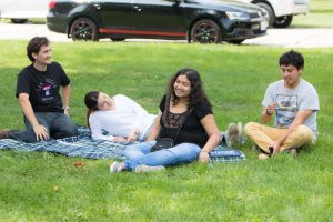 It's not a picnic until you spread a blanket on the grass. Sergey Antipov, Paola Buitrago, Anu Ghosh and Gerald Quiroz share a Technical Division blanket (notice the label on the blanket's front right corner). Photo: Tom Nicol, TD
