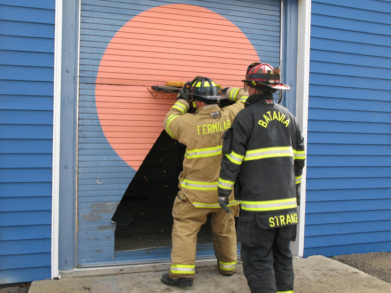 A Fermilab and a Batavia fire department firefighter take a saw to the door. Photo: Chuck Kuhn, BSS