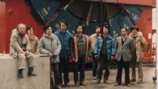 Scientists from the University of Tsukuba and KEK stnad in front of the CDF detector in 1984 at Fermilab. From left: Shoji Mikamo, Yoshio Hayashide, Akihiro Yamashita, Hitoshi Miyata, Kiyoshi Yasuoka,  Taku Yamanaka, Shinhong Kim, Kuni Kondo, Yoshinobu Takaiwa. Photo courtesy of Shinhong Kim