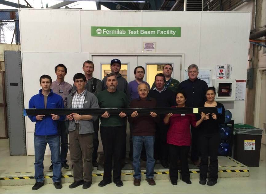 Members of Cosmic Ray VetoGgroup at the Fermilab Meson Test Beam Facility hold a Cosmic Ray Veto counter. Top row, from left: Enhao Song (U. Virginia), Alexander Simonenko (JINR, Dubna), Ralf Ehrlich (U. Virginia), Yuri Oksuzian (U. Virginia), Yuri Davydov (JINR, Dubna), Martin Frank (U. Virginia), Steve Magill (Argonne). Bottom row: Vladimir Baranov (JINR, Dubna), Serdar Kurbanov (U. Virginia), Sten Hansen (Fermilab), Akram Artikov (JINR, Dubna), Shruti Shrestha (Kansas State University), Cristiana Principato (U. Virginia).