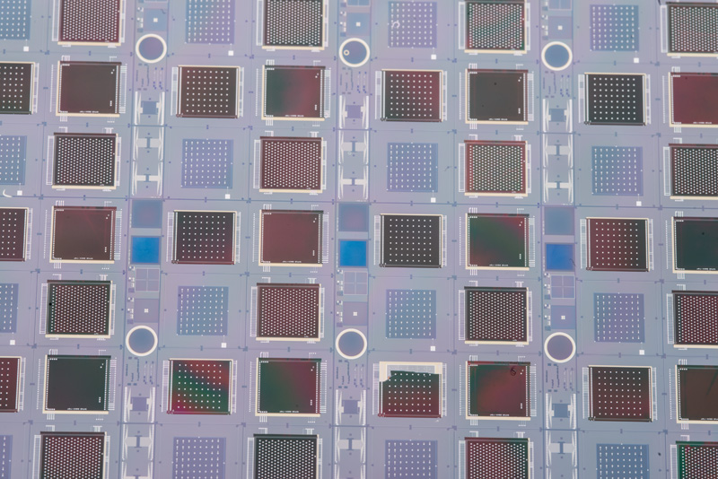Looking at a larger image, you can see three different detector types, distinguished here by their patterns of contacts. One is for the CMS upgrade, another is for a lepton collider, and the third is for X-ray correlation spectroscopy. Fermilab is behind the novel concept of the detector devices and design, which are known as 3-D integrated chips, and company Tezzaron fabricated them. Brookhaven National Laboratory built the sensor. Photo: Reidar Hahn