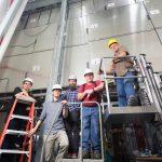 MicroBooNE's shiny new exterior helps scientists identify cosmic rays masquerading as neutrinos. From left: Elena Gramellini, Thomas Mettler. Martin Auger, Mark Shoun, John Voirin. Photo: Reidar Hahn