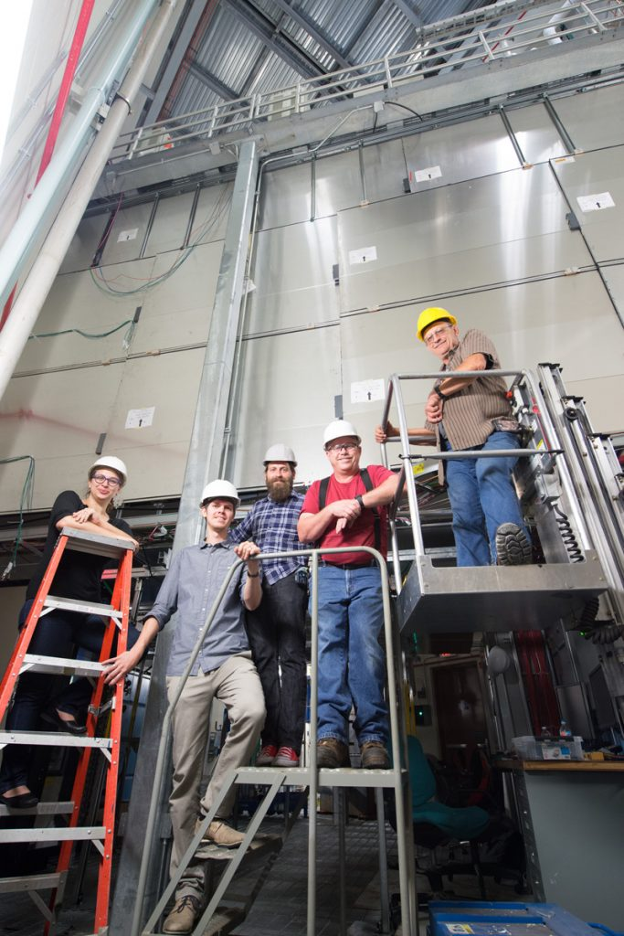 MicroBooNE's shiny new exterior helps scientists identify cosmic rays masquerading as neutrinos. From left: Elena Gramellini, Thomas Mettler. Martin Auger, Mark Shoun, John Voirin. Photo: Reidar Hahn