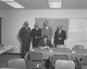 Fermilab founding director Robert Wilson signs the contract with the architectural and engineering company DUSAF in 1967.
