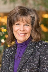 A woman with brown hair smiles in this photo portrait. She wears a purple turtleneck and charcoal blazer.