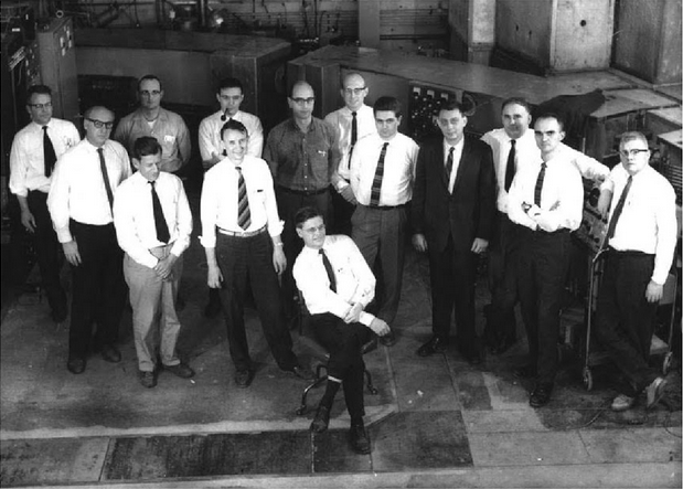 This Cornell University group completed the Cornell 2.2-GeV synchrotron ring in 1964. From left: Don Edwards, Al Silverman, Jack Kenemuth behind Bill Woodward, Maury Tigner behind Boyce McDaniel, Raphael Littauer behind Robert Wilson, Bob Anderson, Bruno Borgia, Peter Stein, Erwin Gabathuler, Karl Berkelman, John DeWire. Photo used with permission from A Personal History of CESR and CLEO by Karl Berkelman, 2004, World Scientific Publishing Co. Pte. Ltd.