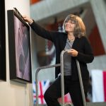 Georgia Schwender puts up a new exhibit in the Fermilab Art Gallery. Photo: Reidar Hahn