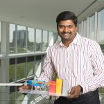 Charles Thanagaraj holds a model of the compact accelerator he recently received a grant to develop. Photo: Reidar Hahn