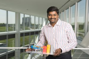 Charles Thanagaraj holds a model of the compact accelerator he recently received a grant to develop. Photo: Reidar Hah