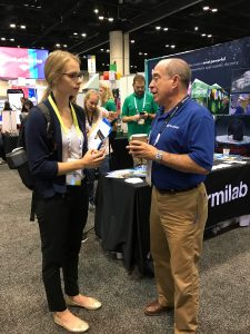 Fermilab CIO Rob Roser chats about Fermilab with an attendee at the 2017 Grace Hopper Conference. Photo courtesy of Tanya Levshina
