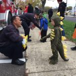 Firefighter Anaya gives candy to a small dinosaur.