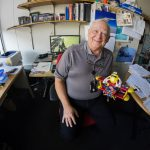 Paul Czarapata in his Accelerator Division office, holding his precious M&M model airplane.