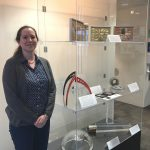 Fermilab Archivist Valerie Higgins stands next to the new permanent display of Fermilab artifacts. Photo: Hannah Ward