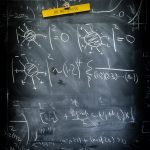 A chalkboard with equations scribbled over it, a magnetic clip holding a yellow piece of paper that reads Do Not Erase.