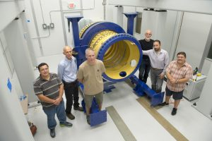 Members of the Fermilab team stand with the lens-holding barrel for the Dark Energy Spectroscopic Instrument. From left: Jorge Montes, Mike Roman, David Butler, Gaston Gutierrez, Giuseppe Gallo and Otto Alvarez. Photo: Reidar Hahn