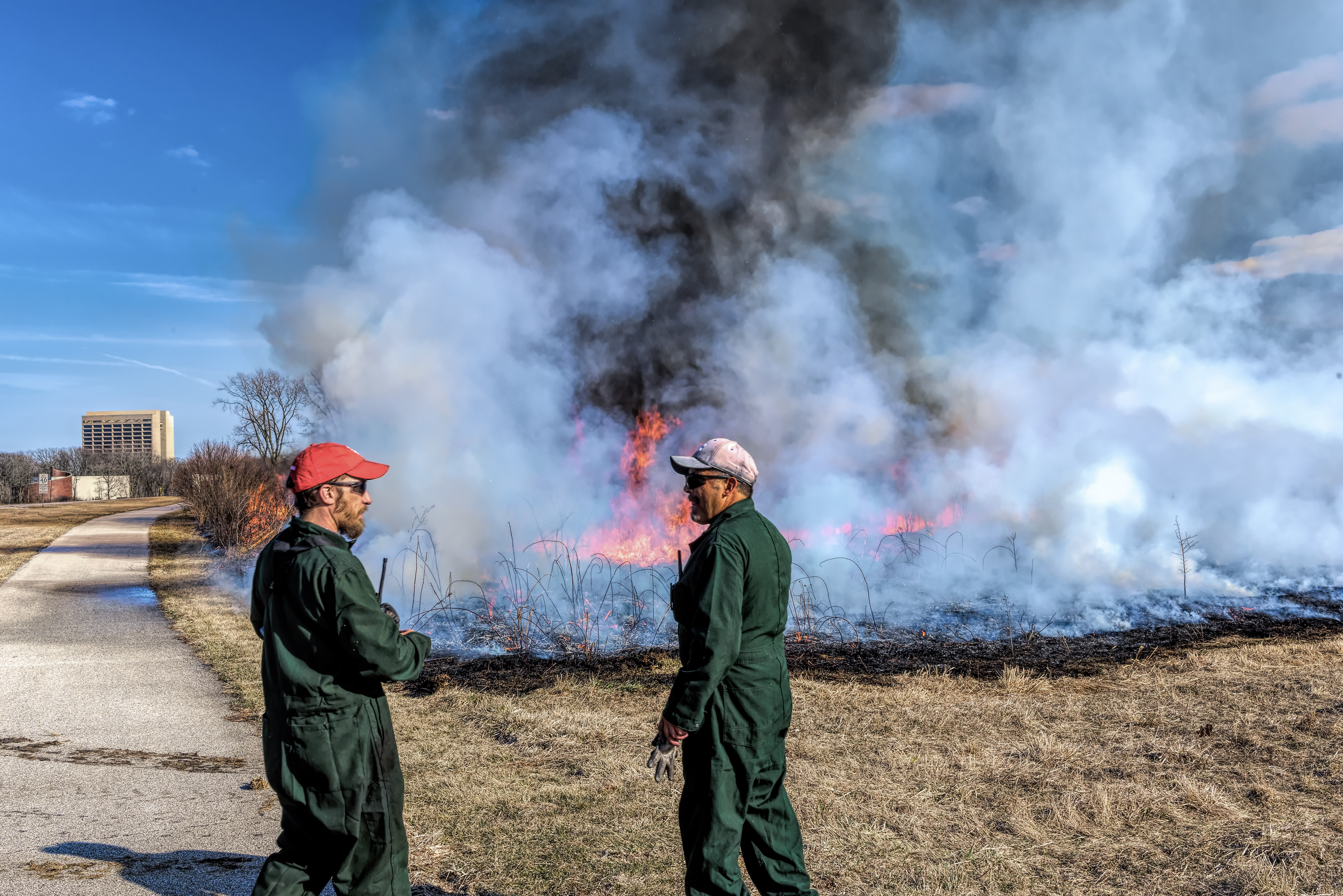 Ryan Campbell (left) and Martin Valenzuela tend to a controlled burn at the Pine Street entrance.