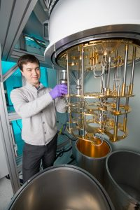 Alex Romanenko prepares to cool superconducting accelerator cavities, the silver-colored objects, to convert it into a quantum device. Photo: Reidar Hahn