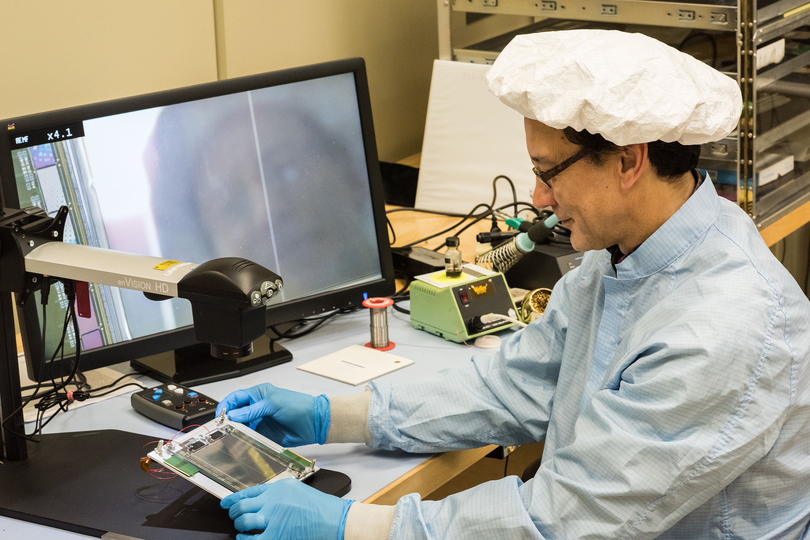 Burt Gonzalez of the Particle Physics Division Detector Development and Operations Department inspects the encapsulation of microbonds for the first 2S electrical high-density interconnect readout design of the CMS outer tracker upgrade. Photo: Leticia Shaddix