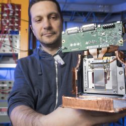 Fermilab engineer Lorenzo Uplegger holds a prototype of the final CMS tracking modules for testing. Photo: Reidar Hahn